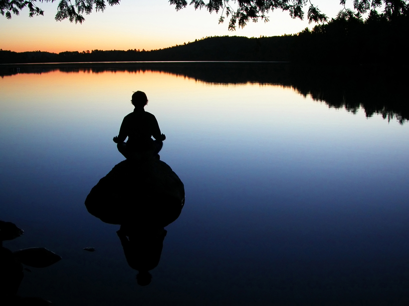 a pic of someone meditating beside a calm lake for their emotional eating treatment